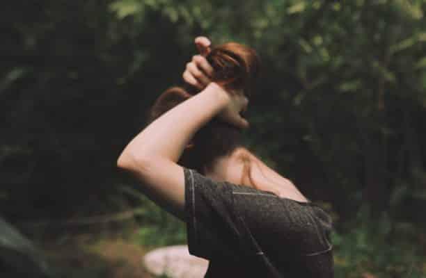 femme qui s'attache les cheveux